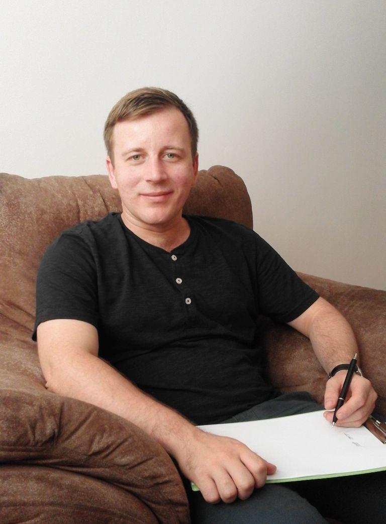 Radosław Piątek trzyma w dłoniach notatnik, w którym zapisuje wszelkie informacje uzyskane podczas spotkania terapeutycznego.